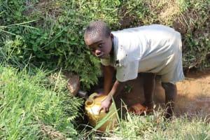 The Water Project: Shisasari Itumbu Community, Mathias Juma Spring -  Justus Collecting Water