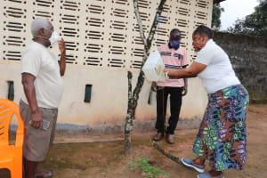 The Water Project: Lungi, Kambia, #6 Bangura St. -  Hygiene Facilitator Teaches Tippy Tap Use