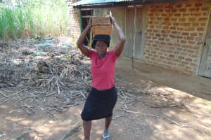 The Water Project: Nguvuli Community, Busuku Spring -  A Woman Carries Bricks To The Spring Site