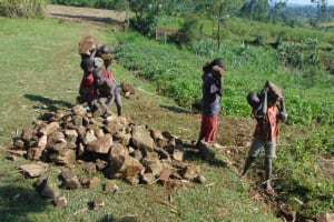 The Water Project: Indulusia Community, Yakobo Spring -  Kids Deliver Rocks To Work Site