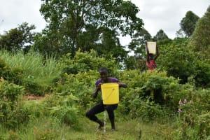 The Water Project: Mundoli Community, Pamela Atieno Spring -  Lifting Water Onto Her Head