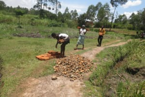 The Water Project: Makale Community, Luyingo Spring -  Community Members Deliver Materials