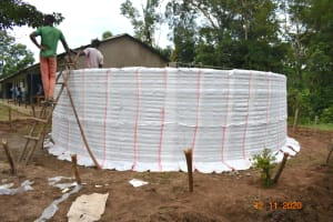 The Water Project: Isango Primary School -  Tying Sugar Sacks To Tank Wire