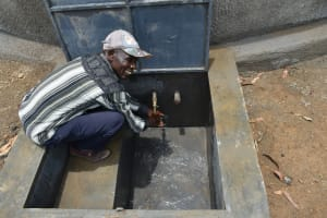 The Water Project: Kinu Friends Secondary School -  A Parent Enjoying Water From The New Tank