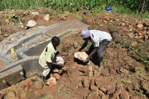 The Water Project: Shitavita Community, Patrick Burudi Spring -  Backfilling With Large Rocks
