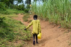 The Water Project: Mundoli Community, Pamela Atieno Spring -  A Child Carrying Water Home