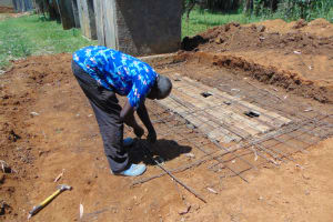 The Water Project: Ivakale Primary School & Community - Rain Tank 1 -  Artisan Moses Obege Setting Latrine Foundation Wire
