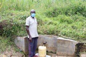 The Water Project: Futsi Fuvili Community, Simeon Shimaka Spring -  John Fetching Water