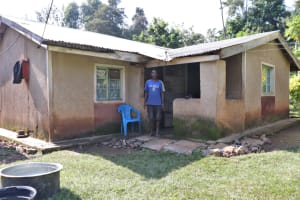 The Water Project: Rosterman Community, Kidiga Spring -  David In Front Of His House