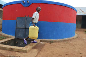 The Water Project: Ivakale Primary School & Community - Rain Tank 1 -  Brian Carries Water From The Tank