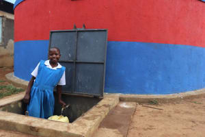 The Water Project: Ivakale Primary School & Community - Rain Tank 1 -  Metrine Collecting Water