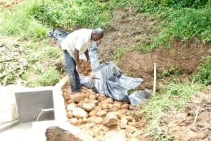 The Water Project: Maraba Community, Nambwaya Spring -  Adding Layer Of Small Rocks