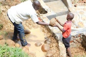 The Water Project: Maraba Community, Nambwaya Spring -  Backfilling With Large Rocks