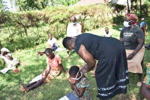 The Water Project: Maraba Community, Nambwaya Spring -  Helping A Girl Put On Her New Mask