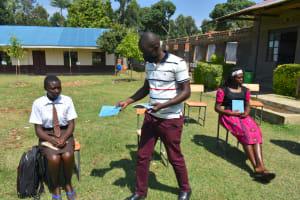 The Water Project: Friends Kisasi Secondary School -  Distributing Training Workbooks