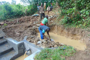 The Water Project: Nguvuli Community, Busuku Spring -  Back Filling With Rocks