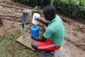 The Water Project: Nguvuli Community, Busuku Spring -  Demonstration On Use And Refiling Of The Chlorine Dispensor