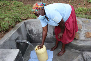 The Water Project: Nguvuli Community, Busuku Spring -  Rosemary Draws Water