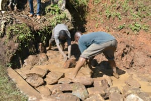 The Water Project: Indulusia Community, Yakobo Spring -  Backfilling With Large Stones