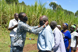 The Water Project: Indulusia Community, Yakobo Spring -  Area Member Of County Assembly Helps A Man Put On A Mask