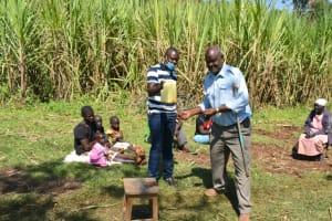 The Water Project: Indulusia Community, Yakobo Spring -  Handwashing Using A Leaky Tin