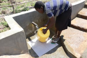 The Water Project: Makale Community, Luyingo Spring -  Washing Her Jerrycan Before Fetching Water