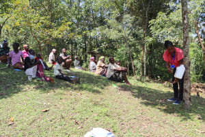 The Water Project: Lukala C Community, Livaha Spring -  Field Officer Christine Demonstrates Leaky Tin Construction