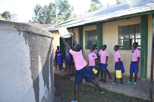 The Water Project: Eshimuli Primary School -  Students Help Cure Rain Tank Cement At Training