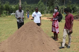 The Water Project: St. Peters Bwanga Primary School -  Field Officers Ian Jacqueline And Erick With School Deputy Headteacher Mr Beselah Assessing The Sand Quality