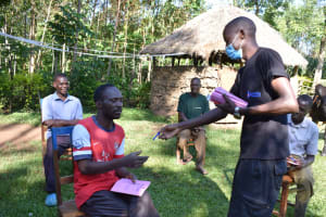 The Water Project: Emusaka Community, Muluinga Spring -  Protus Hands Out Training Workbooks
