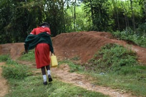 The Water Project: Mukambi Baptist Primary School -  Student Carrying Water From The Spring