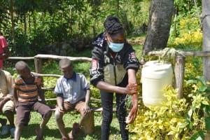 The Water Project: Emusaka Community, Muluinga Spring -  Trainer Elvine Demonstrates Handwashing