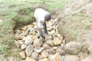The Water Project: Emusaka Community, Muluinga Spring -  Backfilling With Large Rocks