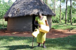 The Water Project: Mbande Community, Handa Spring -  Refilling Her Handwashing Station With Spring Water
