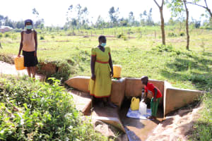 The Water Project: Mbande Community, Handa Spring -  Sarah Fetches Water With Her Kids