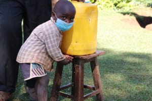 The Water Project: Namarambi Community, Iddi Spring -  Asmans Son Washes His Hands At Home
