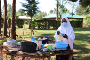 The Water Project: Namarambi Community, Iddi Spring -  Asmans Wife Using Spring Water To Clean Utensils