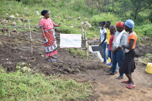 The Water Project: Bukalama Community, Wanzetse Spring -  Reading Through Covid Prevention Reminders Chart
