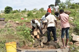 The Water Project: Bukalama Community, Wanzetse Spring -  Community Members Deliver Large Rocks For Backfilling