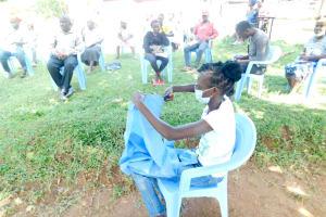 The Water Project: Bukalama Community, Wanzetse Spring -  Cutting Cloth For Mask Making