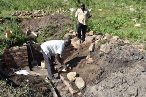 The Water Project: Bukalama Community, Wanzetse Spring -  Stone Pitching To Make Rub Walls