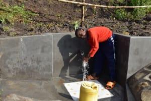 The Water Project: Bukalama Community, Wanzetse Spring -  A Child Washing Hands Before Drinking Water