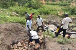 The Water Project: Bukalama Community, Wanzetse Spring -  Backfilling With Large Rocks