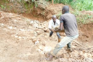 The Water Project: Mukhweso Community, Shemema Spring -  Backfilling With Large Rocks