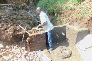 The Water Project: Mukhweso Community, Shemema Spring -  Plastering The Headwall