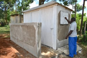 The Water Project: St. Peters Bwanga Primary School -  Artisan Emmanuel Carving The Latrine Inscriptions