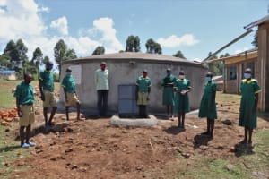 The Water Project: St. Peters Bwanga Primary School -  Teacher And Students Pose Formally At The Rain Tank