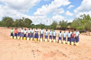 The Water Project: Mang'uu Primary School -  Students Lined Up With Water Containers From Home