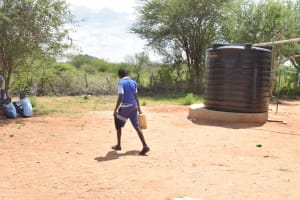 The Water Project: Mang'uu Primary School -  Student Walks By Small Rain Tank Carrying Water
