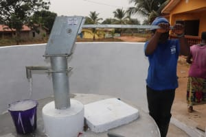 The Water Project: Lungi, New York, Robis, #7 Masata Lane -  Staff Collects Water After Installing Pump